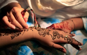 A make-up artist applies henna on a model's hand during a bridal competition in Peshawar